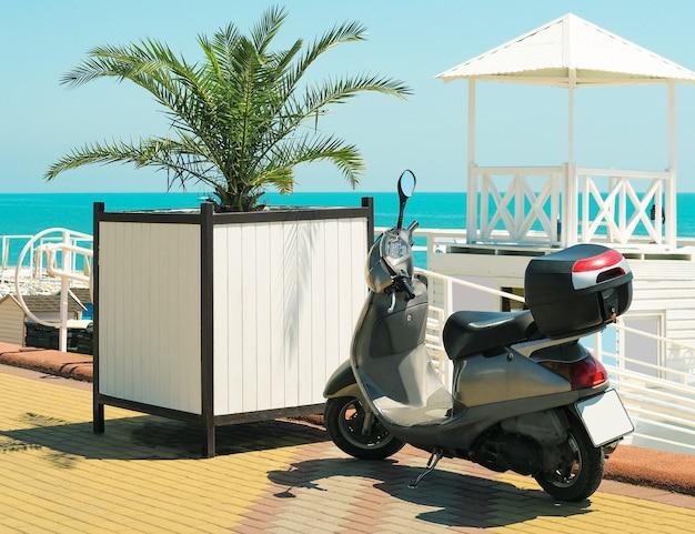 Scooter garé à l'extérieur sur la plage et le fond des feuilles de palmier au jour d'été ensoleillé