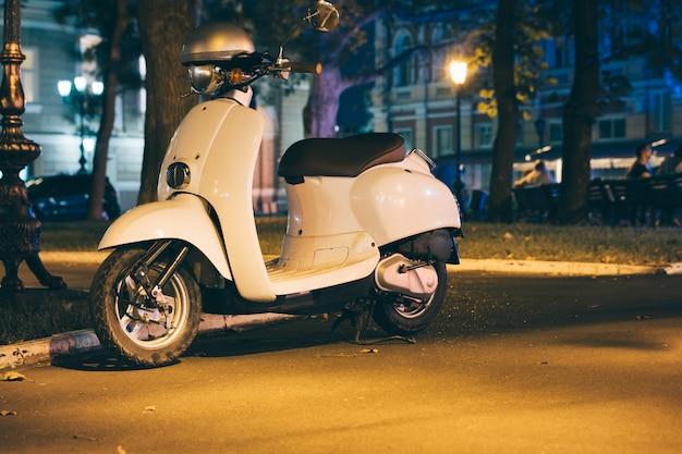 Scooter à moteur blanc dans une ville de nuit