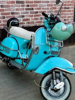 Scooter rétro bleu avec casque accroché au volant garé dans la rue