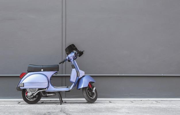 Scooter vintage devant le fond de mur gris