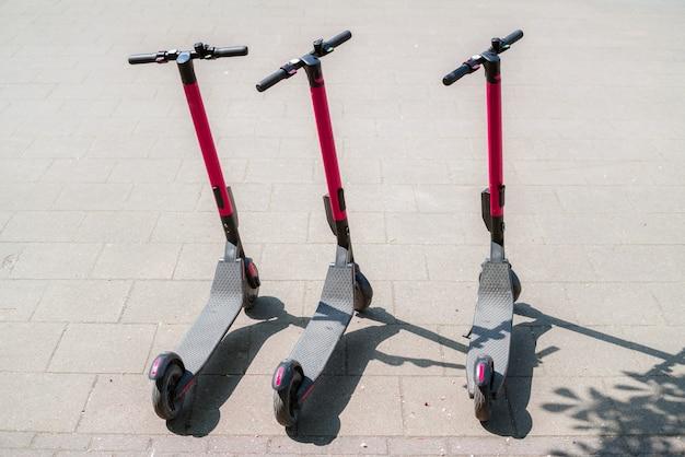Scooters de ville électriques écologiques modernes à louer à l'extérieur sur le trottoir.