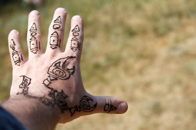 Scorpion arabe mehendi dessinant sur une main d'homme