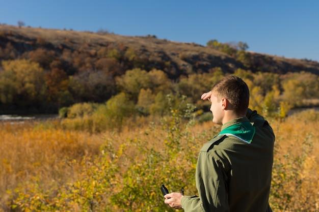 Scout essayant de s'orienter alors qu'il se tient dans la nature sauvage en regardant le soleil avec un compas magnétique à la main pour la navigation