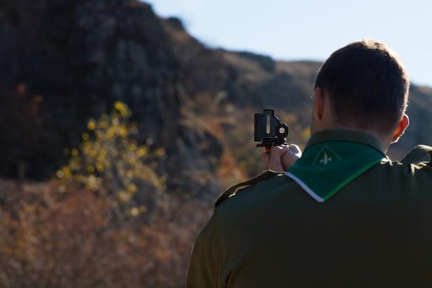 Scout naviguant dans le désert en prenant une lecture sur un sommet de montagne avec son compas magnétique pour établir son emplacement, vue de derrière