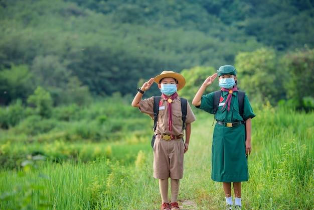 Scouts étudiants asiatiques portant des uniformes et un masque