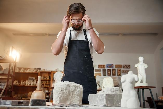 Sculpteur masculin en chemise blanche et tablier noir fait une copie en calcaire de torse de femme au studio artistique.