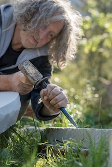 Sculpteur principal avec ciseau et marteau dans la pierre à l'extérieur.