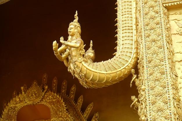 Sculpture dorée de naga sur la porte du temple wat sri panthon.