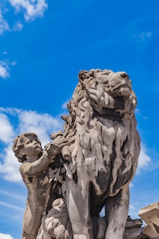 Sculpture du lion conduit par un enfant au pont alexandre iii à paris