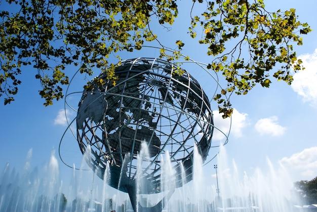 Sculpture en métal du globe terrestre sur une source d'eau