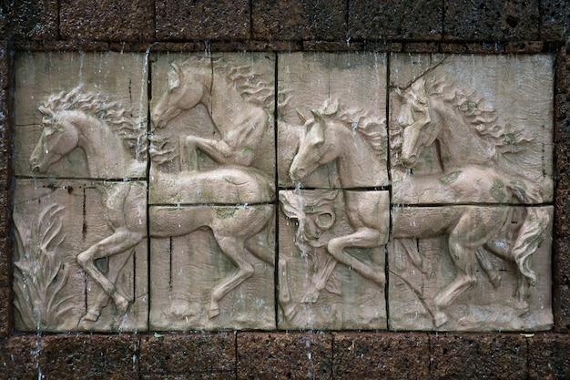 Sculpture sur pierre de chevaux sur le mur avec chute d'eau