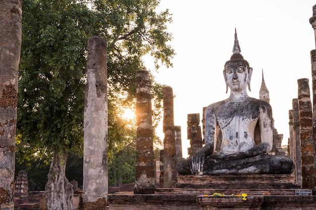 Sculpture statue de bouddha debout de wat mahathat dans le parc national de sukhothai en thaïlande au coucher du soleil.