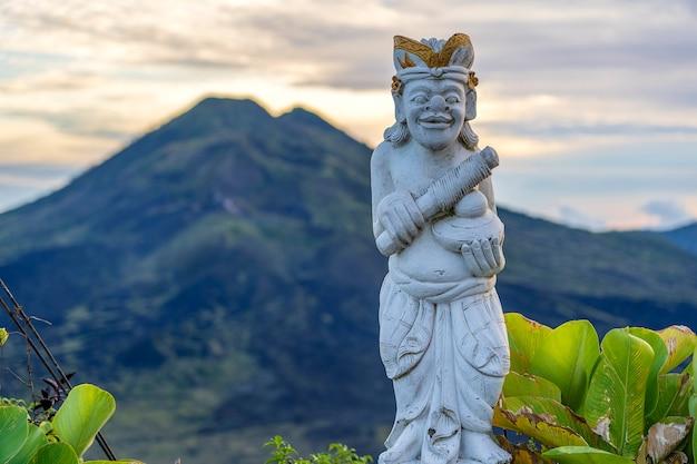 Sculpture traditionnelle balinaise sur fond de volcan batur au lever du soleil, le matin. île de bali, indonésie. fermer