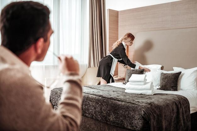 Se comporter immoral. homme d'affaires aux cheveux noirs se comportant de manière immorale en regardant la femme de chambre de l'hôtel travailler