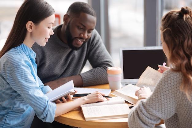 Se concentrer exprès. jolie jeune femme pointant sur livre alors qu'il était assis à la bibliothèque légère parmi ses co-étudiants internationaux