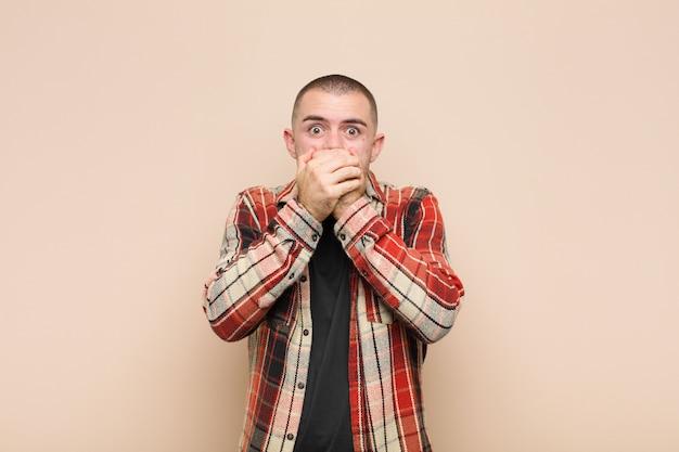 Se couvrir la bouche avec les mains avec une expression choquée et surprise, garder un secret ou dire oups