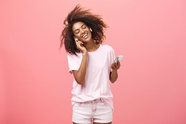 Se débarrasser des soucis avec de bons airs dans les oreilles. heureuse jeune femme africaine séduisante en tenue tendance écoutant de la musique dans des écouteurs sans fil touchant des écouteurs souriant dansant et tenant un smartphone