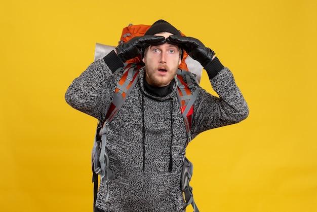 Se demandait un auto-stoppeur avec des gants en cuir et un sac à dos observant