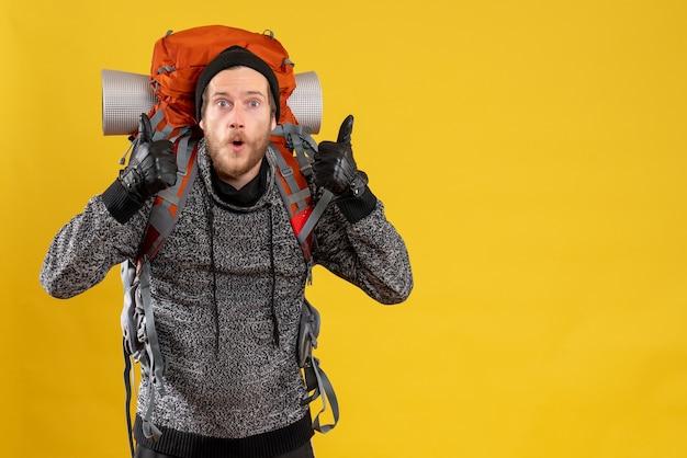 Se demandait un auto-stoppeur masculin avec des gants en cuir et un sac à dos abandonnant les pouces
