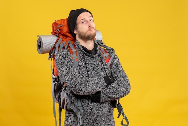 Se demandait un auto-stoppeur masculin avec des gants en cuir et un sac à dos croisant les mains