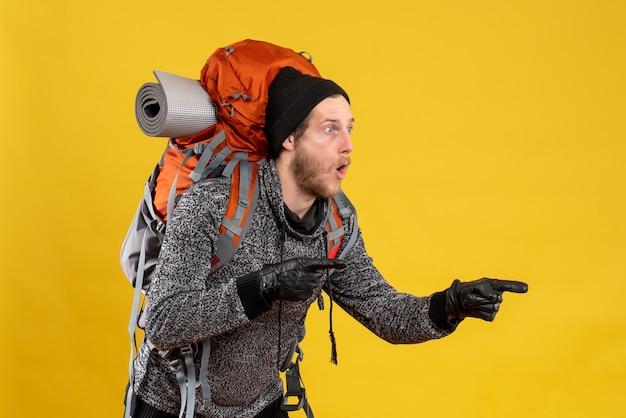 Se demandait un auto-stoppeur masculin avec des gants en cuir et un sac à dos regardant quelque chose