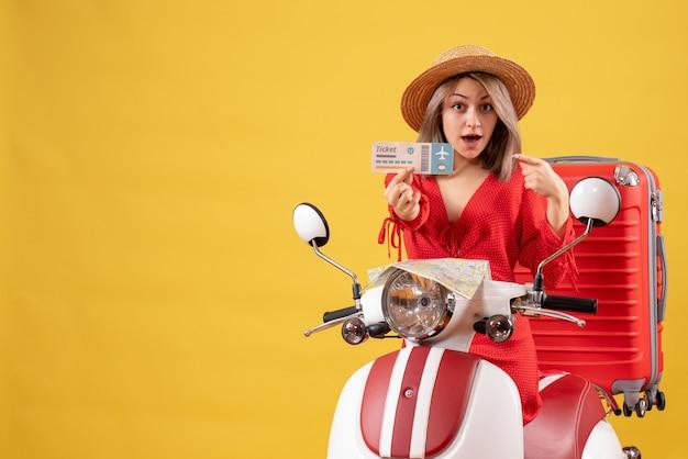 Se demandait une jeune femme sur un cyclomoteur avec une valise rouge tenant un billet