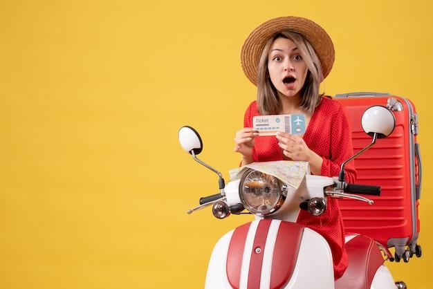 Se demandait une jeune femme en robe rouge tenant un billet d'avion sur un cyclomoteur