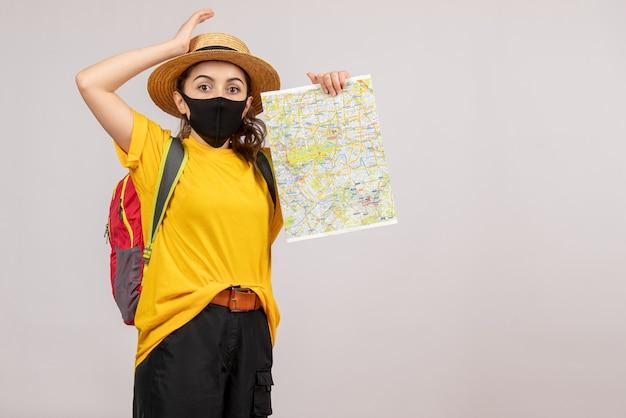 Se demandait une jeune femme avec un sac à dos tenant une carte sur fond gris