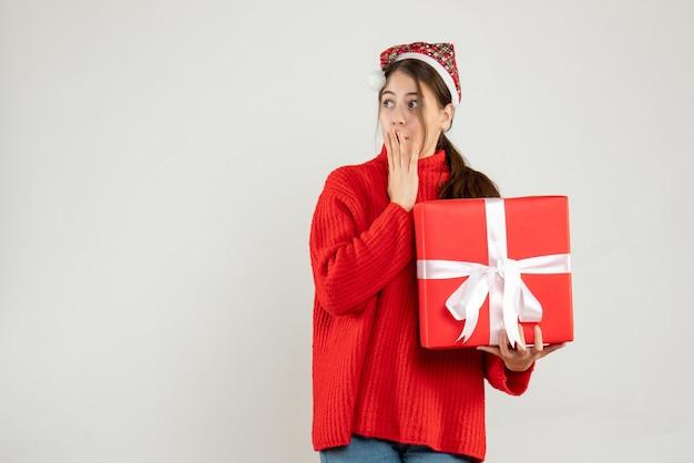Se demande fille avec bonnet de noel mettant la main à sa bouche tenant cadeau sur blanc