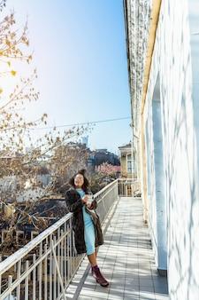 Se détendre au soleil. femme à la mode joyeuse reposant sur son large balcon et à la satisfaction