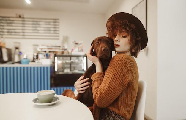 Se détendre avec un chiot dans un café pour une tasse de boisson chaude