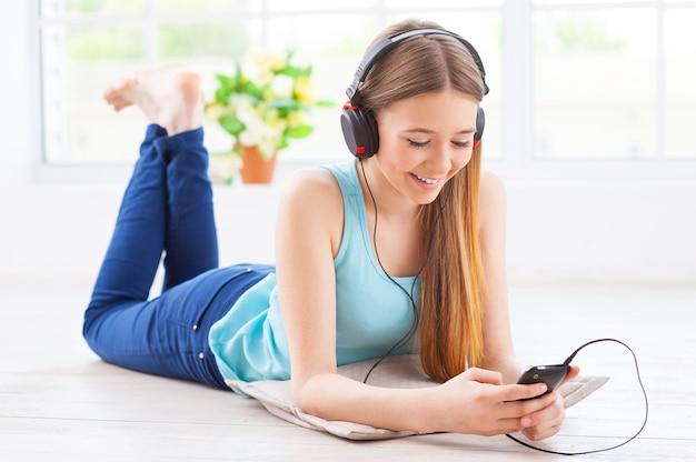 Se détendre avec sa musique préférée. adolescente gaie dans des écouteurs écoutant la musique tout en se couchant sur le plancher à son appartement