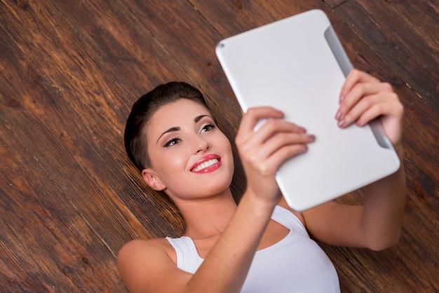 Se détendre avec sa toute nouvelle tablette. vue de dessus de la belle jeune femme aux cheveux courts tenant une tablette numérique et souriant en position couchée sur le plancher de bois franc