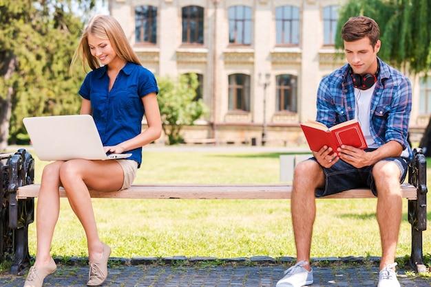 Se détendre séparément. beau jeune homme assis sur le banc et lisant un livre tandis que belle femme assise près de lui et utilisant un ordinateur