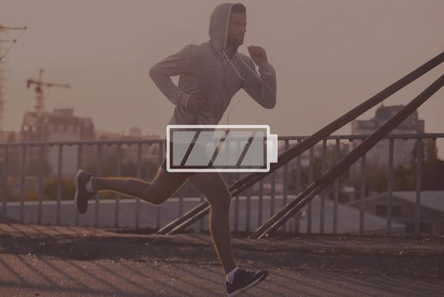 Se diriger vers son objectif. vue latérale d'un jeune homme confiant qui court le long du pont