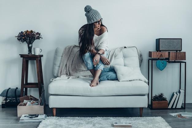 Se donner le temps de rêver. jeune femme réfléchie en tenue décontractée à l'écart