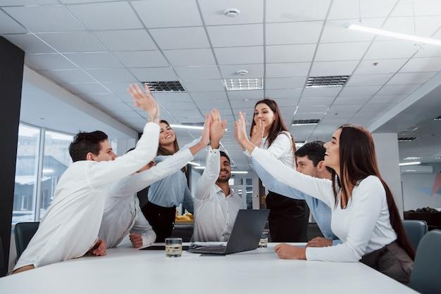 Se féliciter mutuellement. la tâche est finie. un groupe d'employés de bureau heureux de battre leurs propres records et de réussir