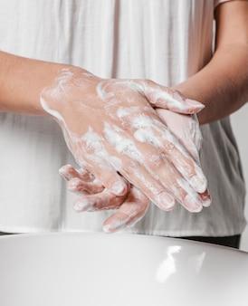 Se laver les mains en frottant avec du savon vue de face