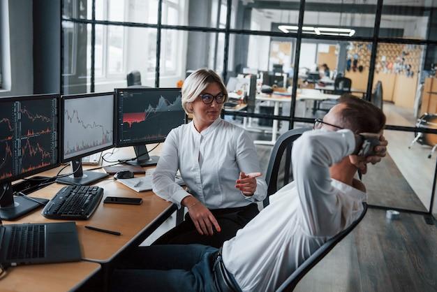 Se parler. deux agents de change en tenue de soirée font une pause au bureau.