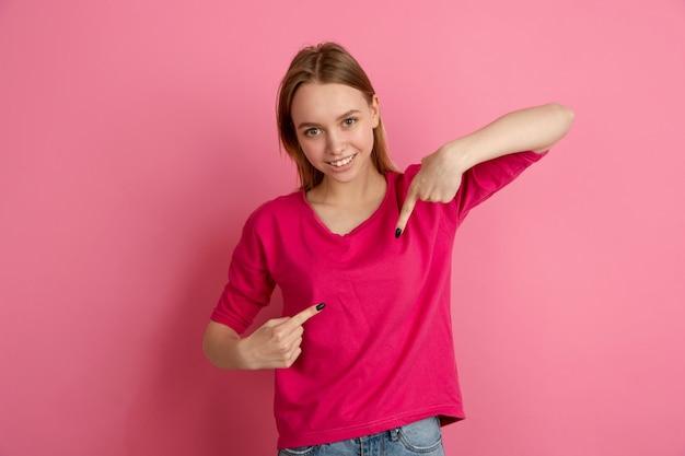 Se pointant du doigt. portrait de jeune femme caucasienne isolé sur mur rose, monochrome. beau modèle féminin. concept d'émotions humaines, expression faciale, tendance.