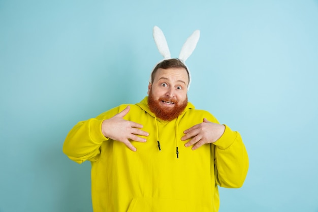 Se pointer du doigt. homme de race blanche comme un lapin de pâques avec des vêtements décontractés lumineux sur fond bleu studio.