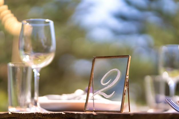 Se préparer pour une fête en plein air. décoré de tables de fleurs fraîches servies. numéro de table. détails de décoration