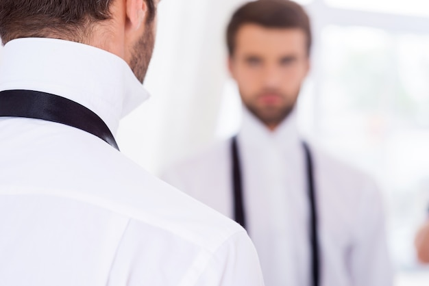 Se préparer pour une journée spéciale. vue arrière du jeune homme en chemise blanche et cravate déliée debout contre miroir