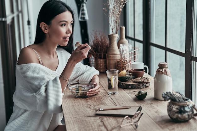 Se préparer pour une longue journée. jolie jeune femme mangeant un petit déjeuner sain