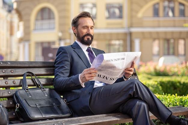 Se procurer plus d'information. agréable homme d'affaires concentré lisant un journal assis sur le banc