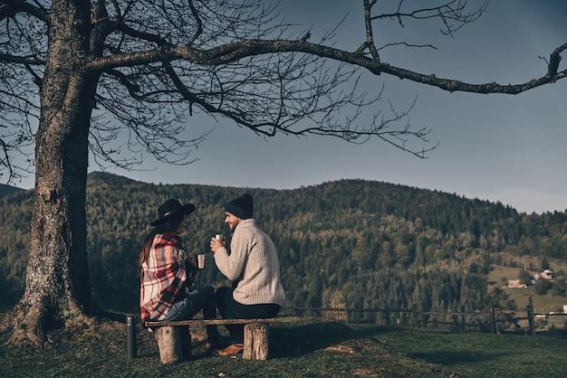 Se réchauffer avec des boissons. jeune couple buvant un tee chaud alors qu'il était assis sur le banc dans les montagnes