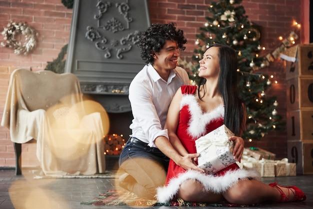 Se regarder avec amour. beau couple célébrant le nouvel an dans la salle décorée avec arbre de noël et cheminée derrière