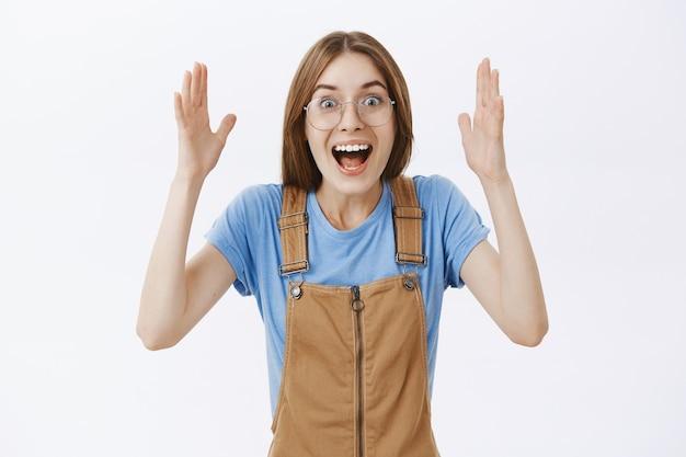 Se réjouir d'une jolie fille heureuse levant les mains émotionnelles, ayant des nouvelles incroyables, triomphant ou célébrant