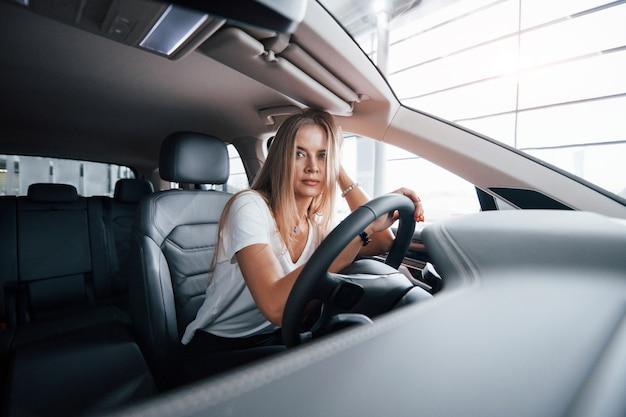 Se sent fatigué. fille en voiture moderne dans le salon. le jour à l'intérieur. acheter un véhicule neuf
