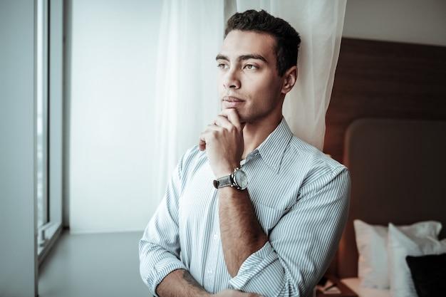 Se sentir attentionné. homme d'affaires aux yeux sombres se sentant réfléchi tout en pensant à l'ouverture d'une nouvelle succursale